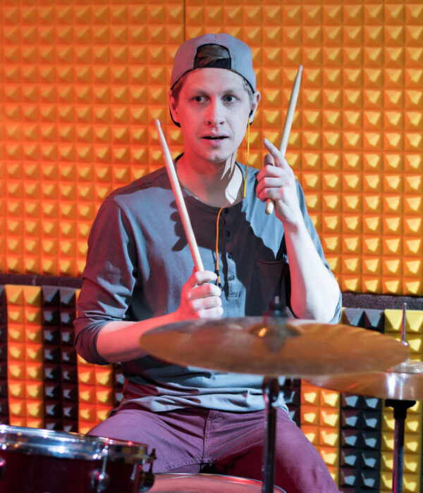 Portrait of young man playing drums performing in dim recording studio while making new album with his band, copy space